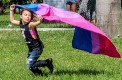 Jaelyn Benson running in the housing lawn with a flag during Pride Fest Mohammed F Emran | Staff Photographer