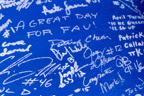 The front wall of the store is covered in the signatures of FAU athletes. Photo by Jasmyn Williams.