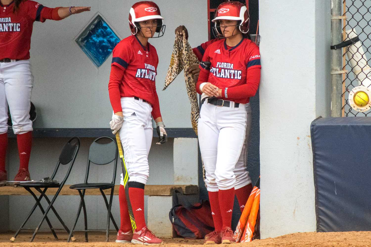 Christina (left) and Melissa Martinez wait in the dugout for their respective turns at bat. Ryan Lynch | Multimedia Editor