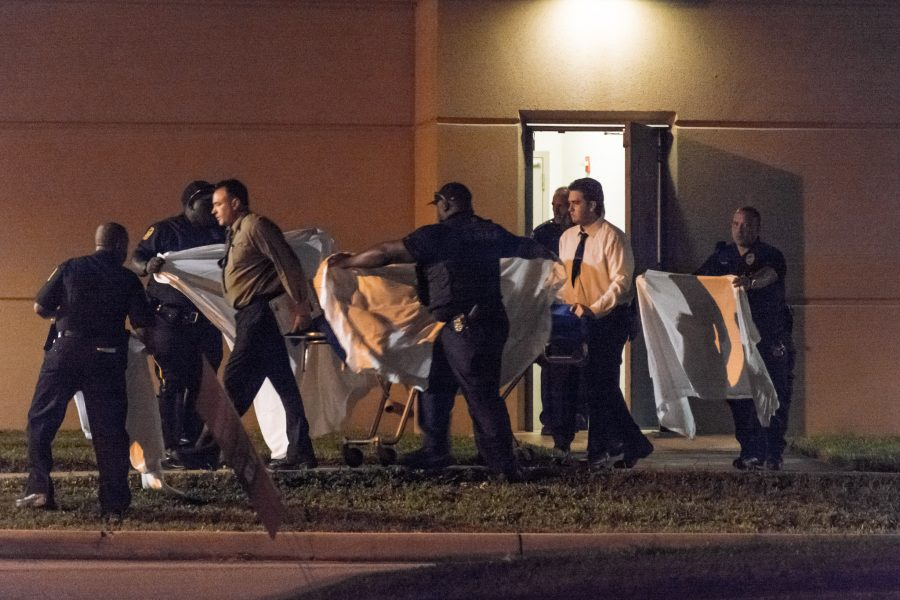 FAU Police officers and other personnel escort a stretcher to a waiting van. Jonathan Scott | Contributing Photographer