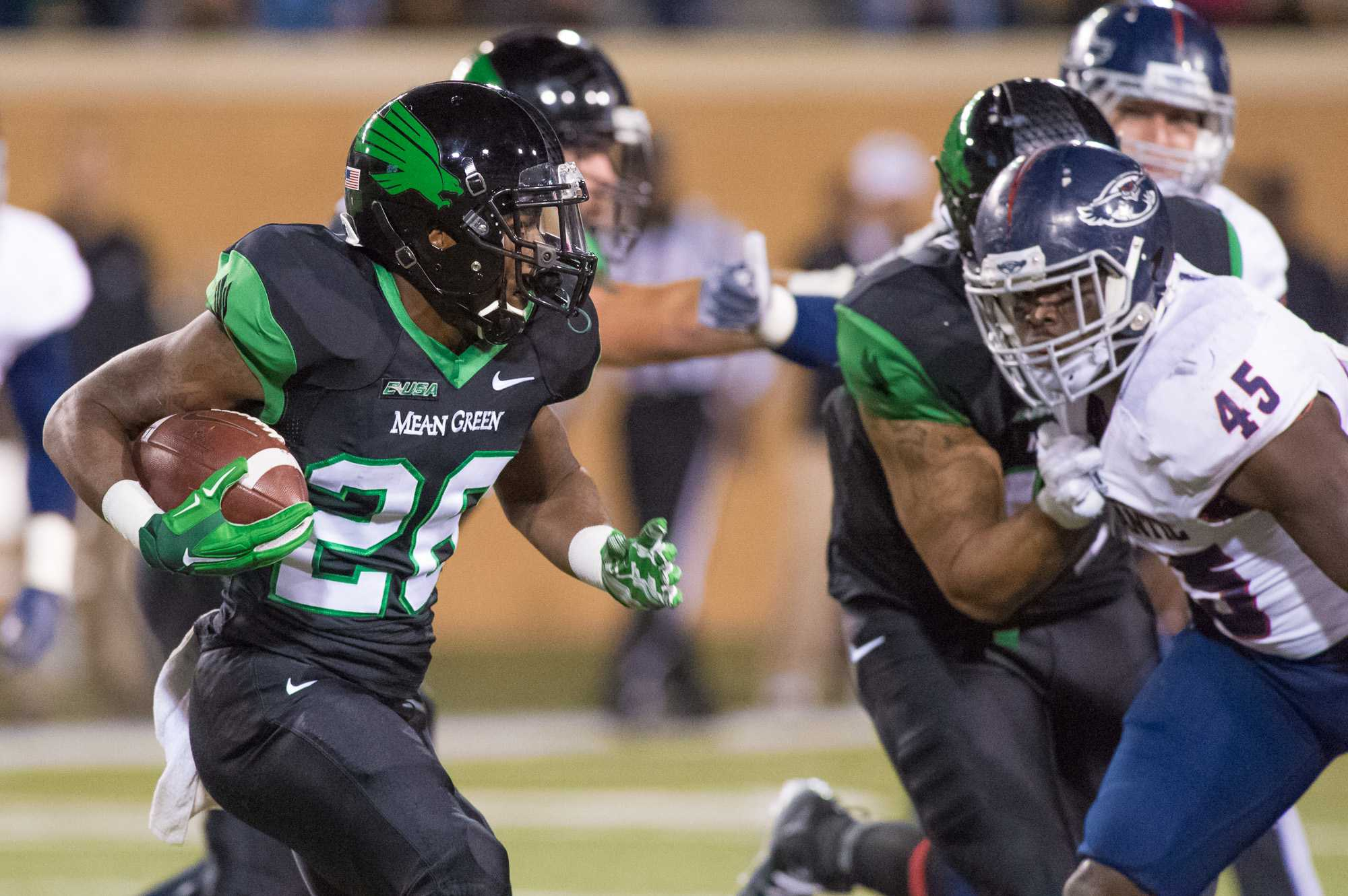 [ Max Jackson | Photo Editor ] North Texas running back Jeffrey Wilson picks up a first down with a five yard run in the first quarter. FAU linebacker Andrae Kirk is in pursuit.