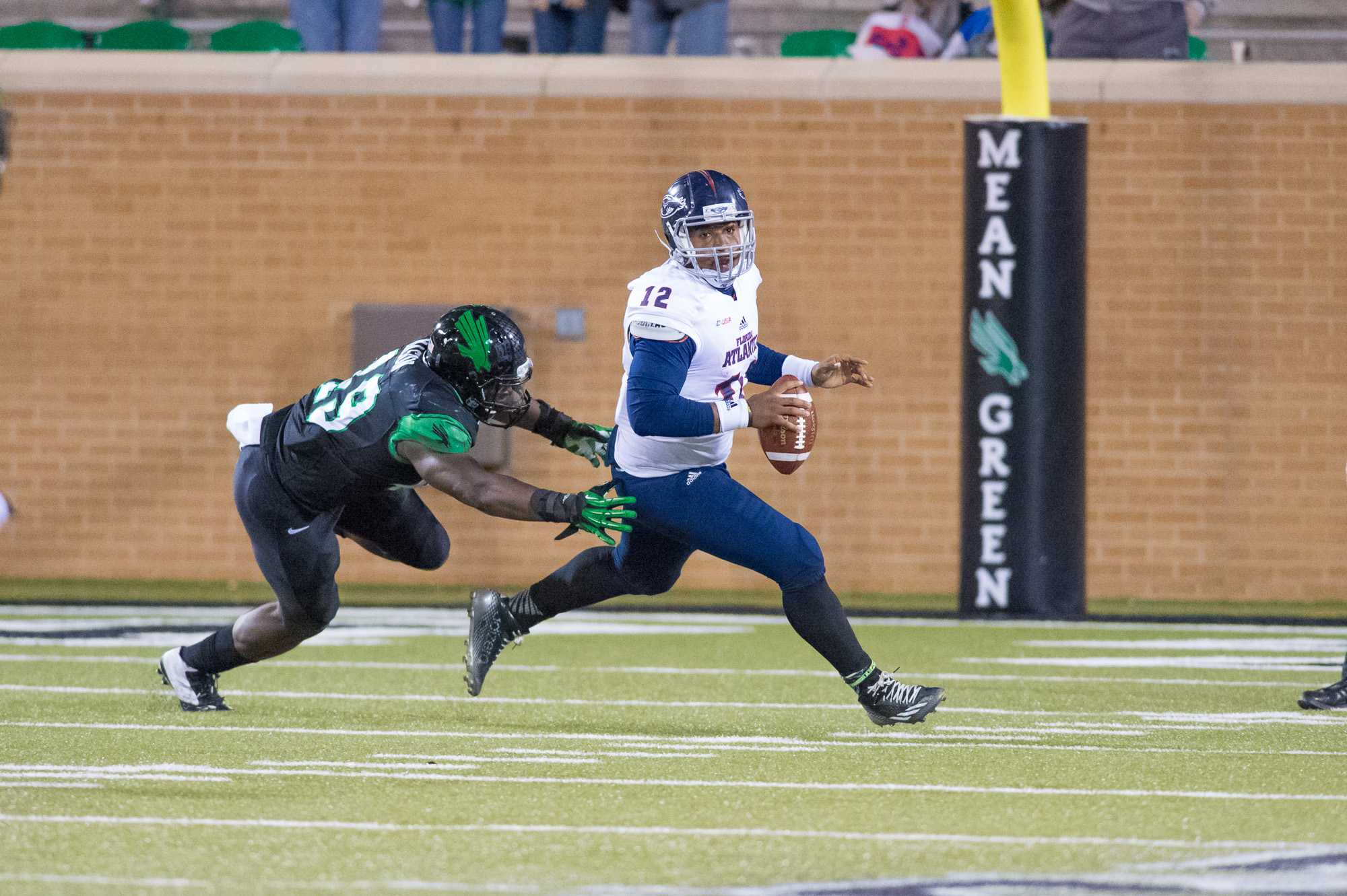 [ Max Jackson | Photo Editor ] Jaquez Johnson evades a North Texas defender to attempt a pass.  Johnson passed for 99 yards, threw one interception and was sacked three times.