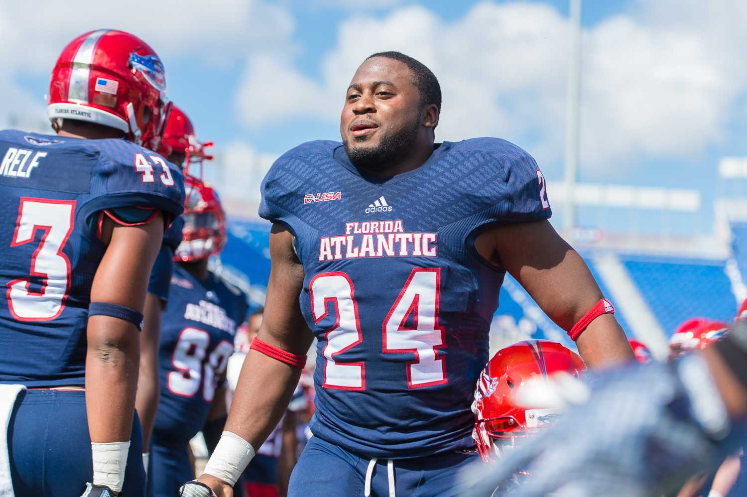 FAU senior running back Tony Moore walks through the human tunnel of teammates during the Senior Day Celebration prior to the game.