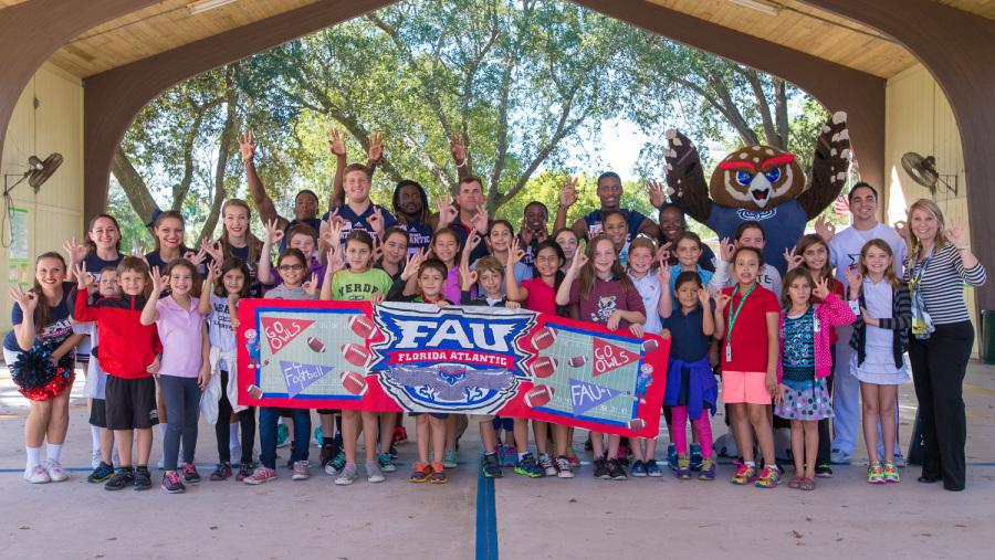 Students of Verde Elementary in Boca Raton gather for a photo with FAU Football players, cheerleaders and Coach Partridge while holding the banner they made for the Red Blue Spring game. The students won a contest for designing the best banner and were awarded a visit from FAU athletes.  Photo by: Max Jackson