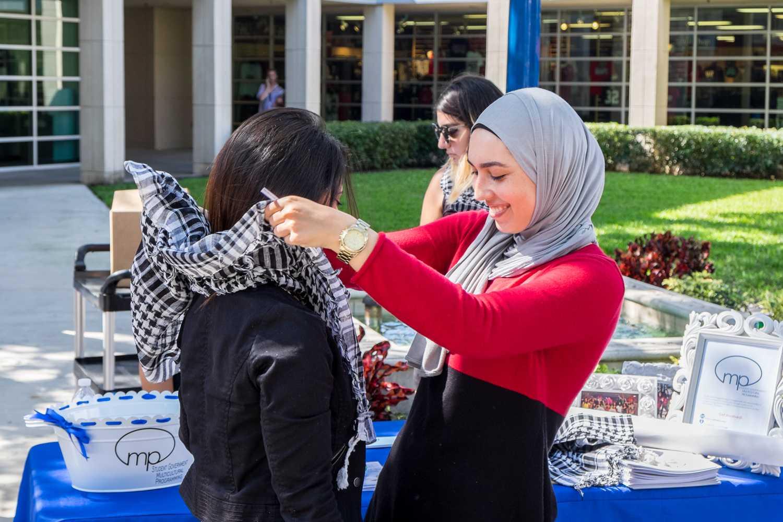 SJP member showing a student on how to wear a keffiyeh.  [ Mohammed F Emran | Web Editor ]