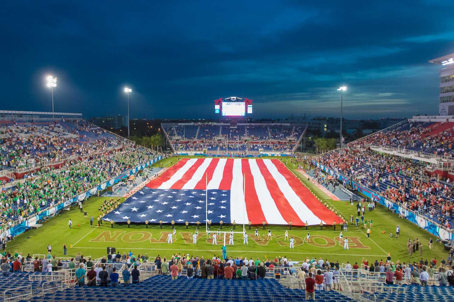 A 100-yard long American flag is held out during the singing of the National Anthem prior to the first-ever kick off of the Boca Raton Bowl.