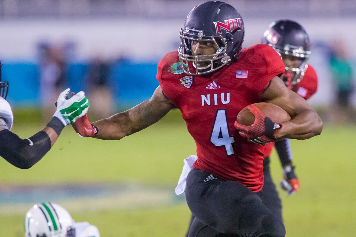 Da'Ron Brown (4) of the Northern Illinois Huskies throws a stiff arm to pick up yards in the second half of the Boca Raton Bowl.