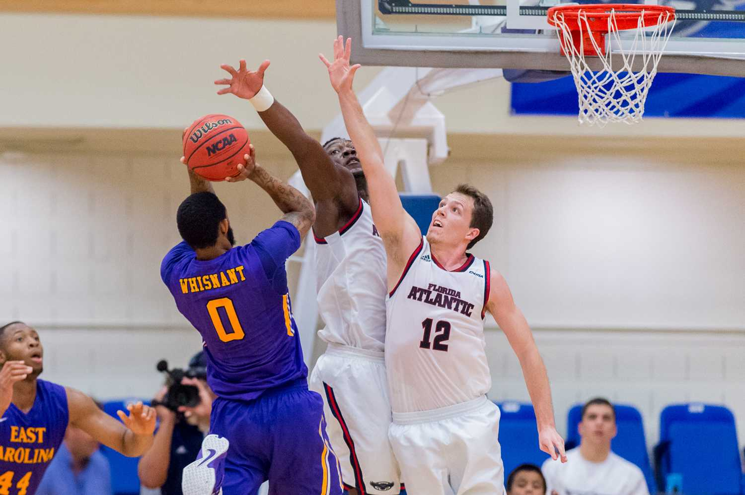 FAU guards Jackson Trapp and C.J. Turman attempt to stop Eastern Carolina guard Terry Whisnant from scoring.