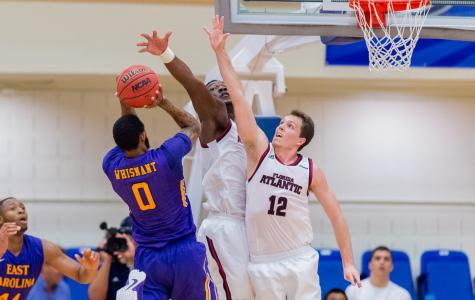 Both center C.J. Turman and guard Jackson Trapp (12) go for a block in a 72-63 win over East Carolina University earlier this season. Photo by Max Jackson