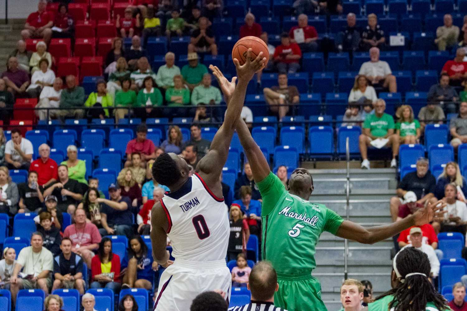 FAU's C.J. Turman (0) and Marshall's Cheikh Sane (5) at tip-off.