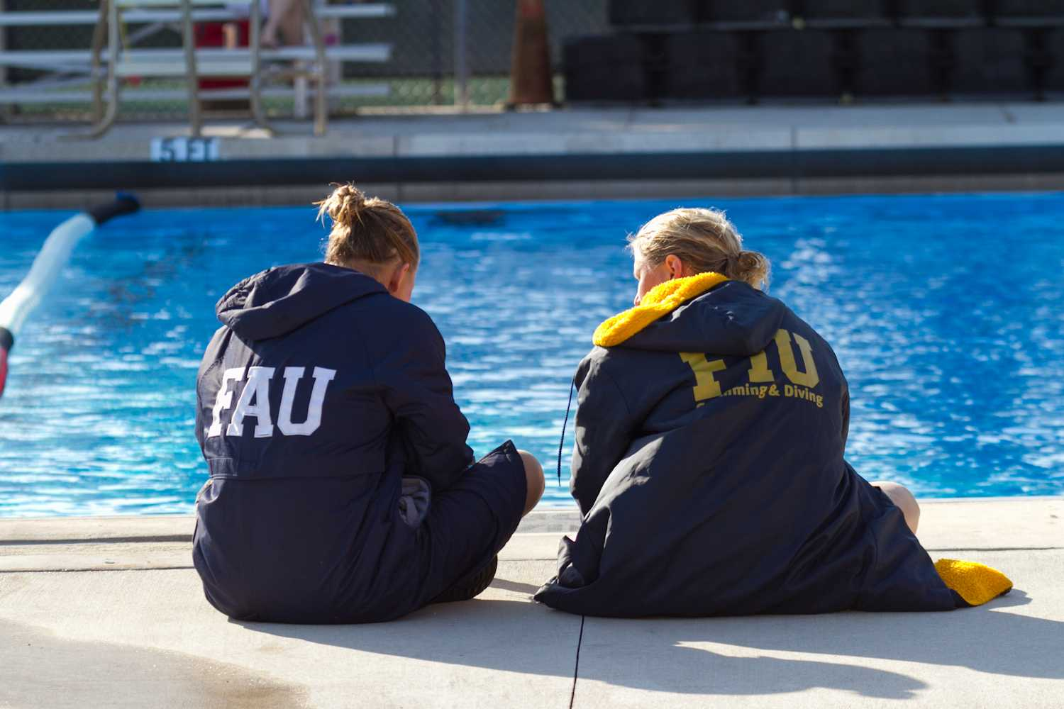 Two swimmers from FAU and FIU sit aside the pool during a break in the meet.