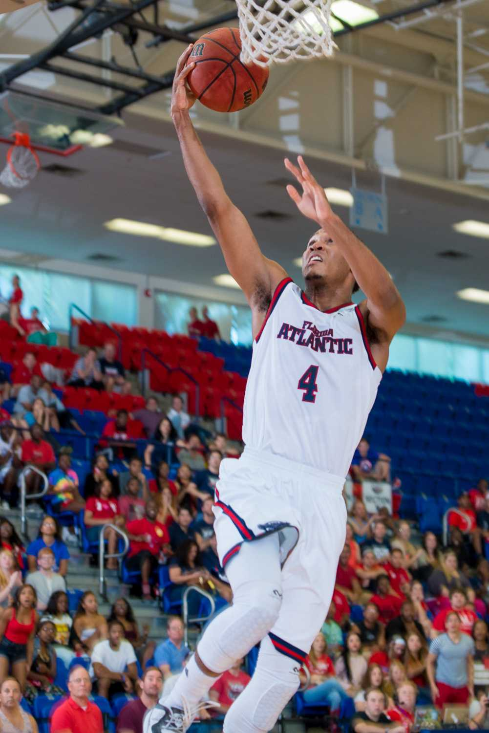 FAU freshman guard Justin Massey (4) ends the first half with a successful layup to bring the score to 25-28 FIU.