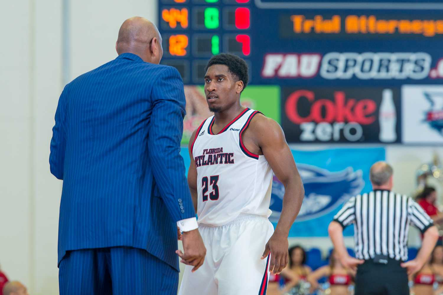 FAU head coach Michael Curry speaks with guard Solomon Poole (23) after an FIU basket in the beginning of the second half.