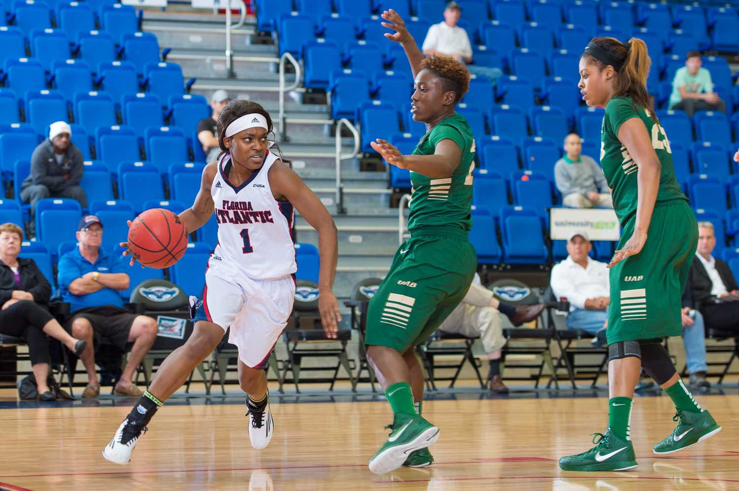 FAU guard, Aaliyah Dotson (1) looks for room under the basket while Chelsee Black (21) attempts to block her.