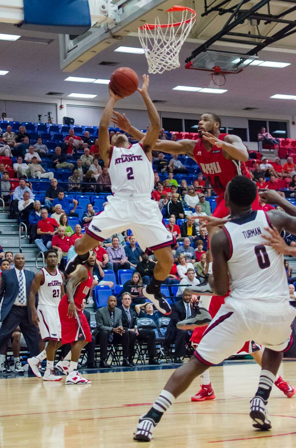 Owl's guard, Marquan Botley (2) makes his way around WKU defenders to take a shot from under the hoop.