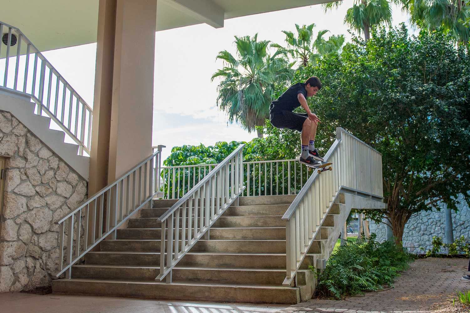 A student from Henderson Middle School on FAU's campus attempts a trick on his skateboard in the breezeway.