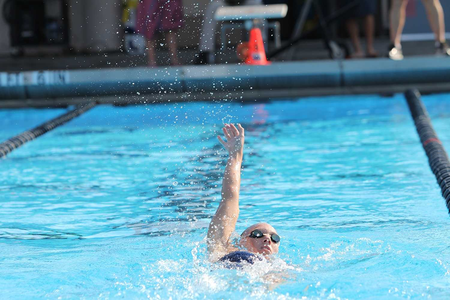 Megan Reuter of FAU does the backstroke at FAU's meet against FIU.