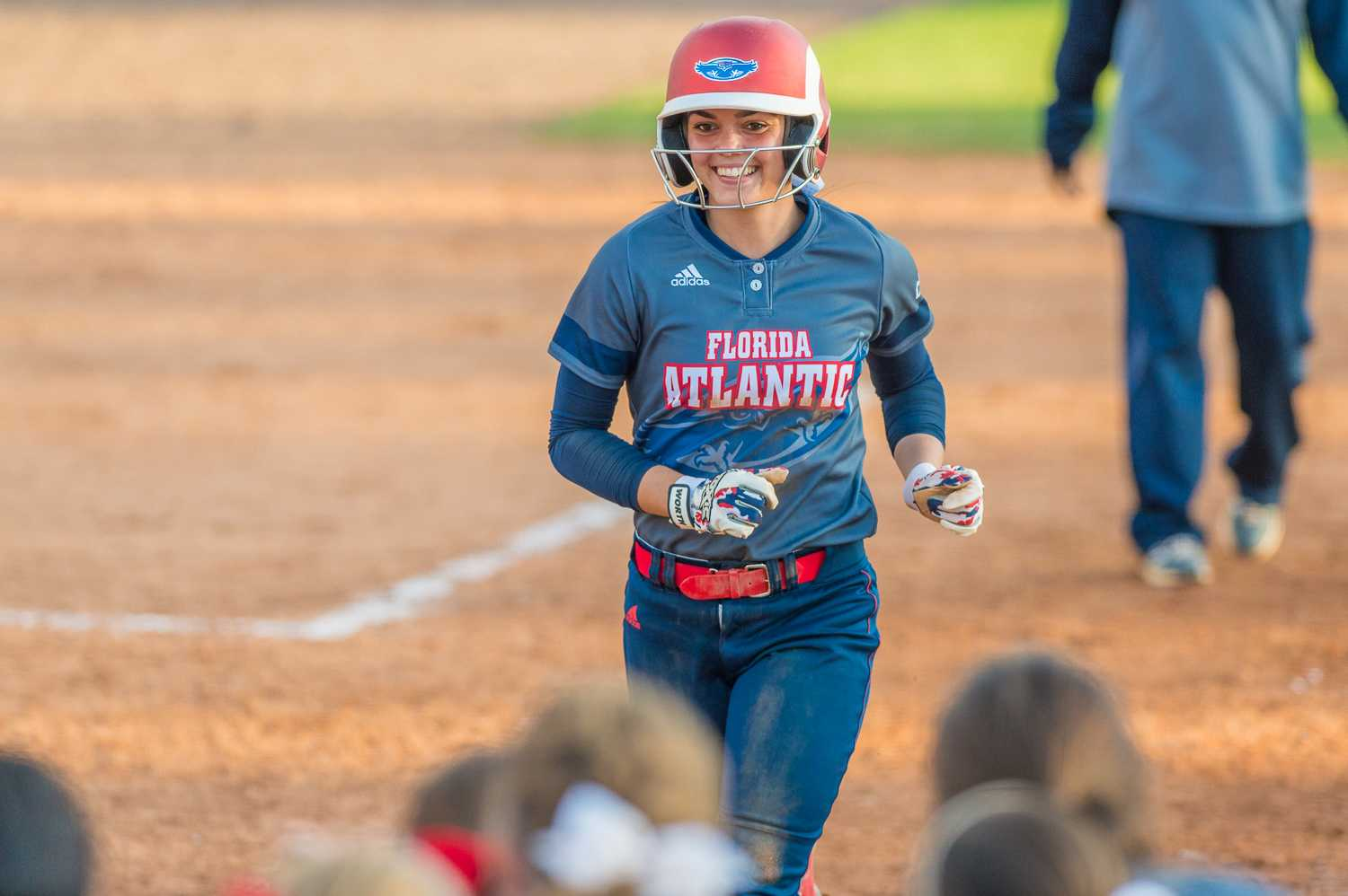 Melissa Martinez (3) smiles as she runs towards teammates gathered around home plate after her two-run home run in the third.