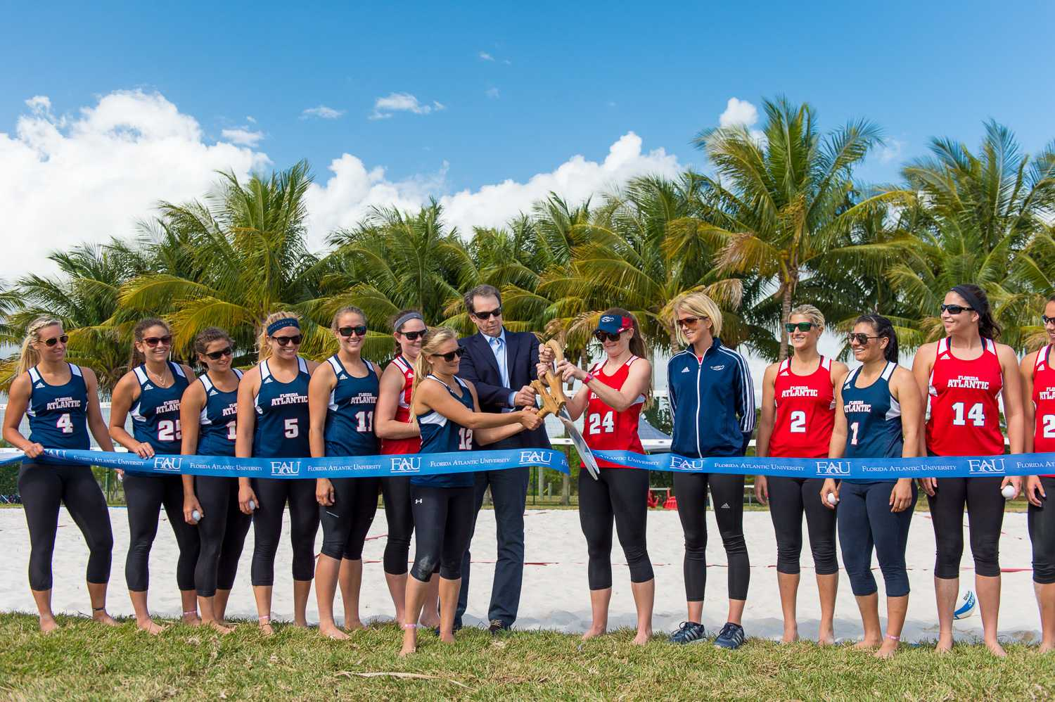 FAU sand volleyball captains Natalie Fraley (12) and Mandy McIntosh (24) are joined by FAU President John Kelly to cut the ribbon to officially open the new sand volleyball courts.