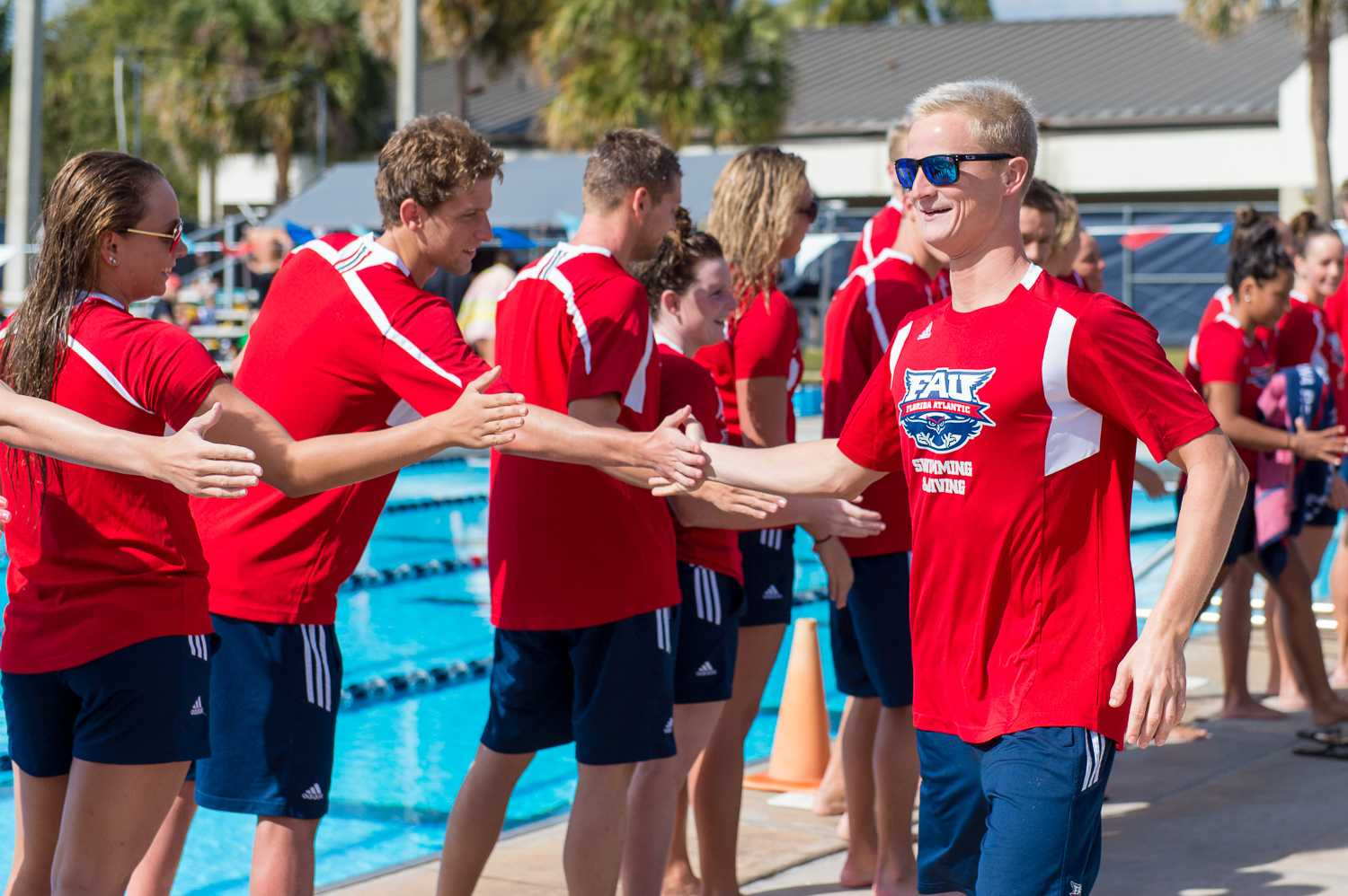 Team captain Richard Andrews (right) from FAU high-fives his teammates during the senior send-off ceremony prior to the start of the meet.  Andrews won the men's 200 freestyle with a time of 1:42.17.