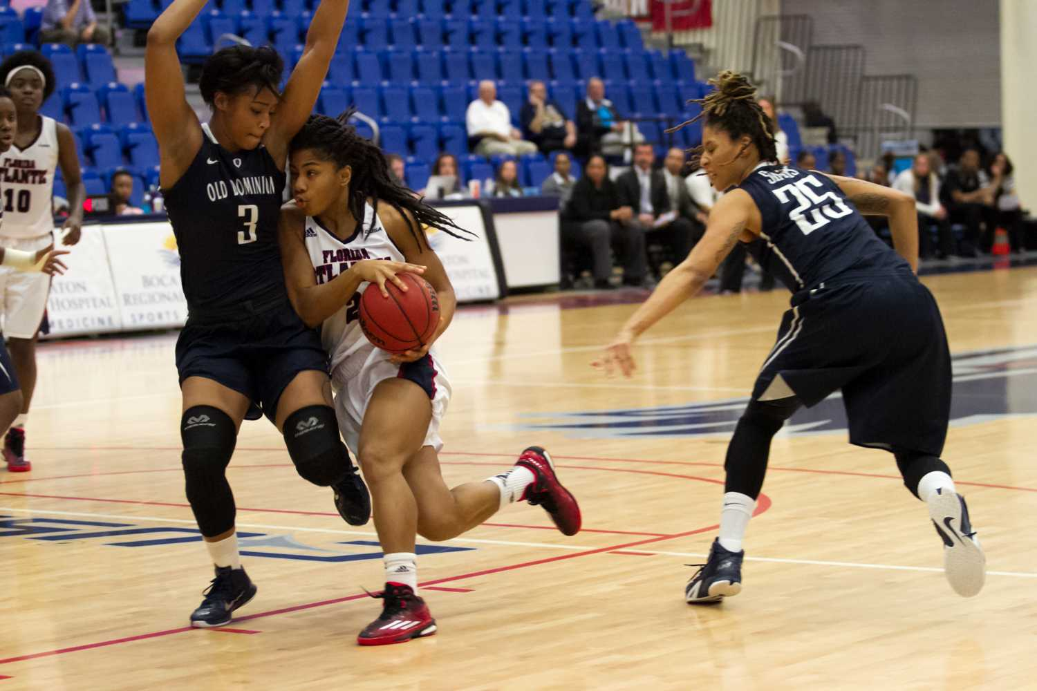 Shaneese Bailey drives towards the rim, holding off Chelisa Painter (3).
