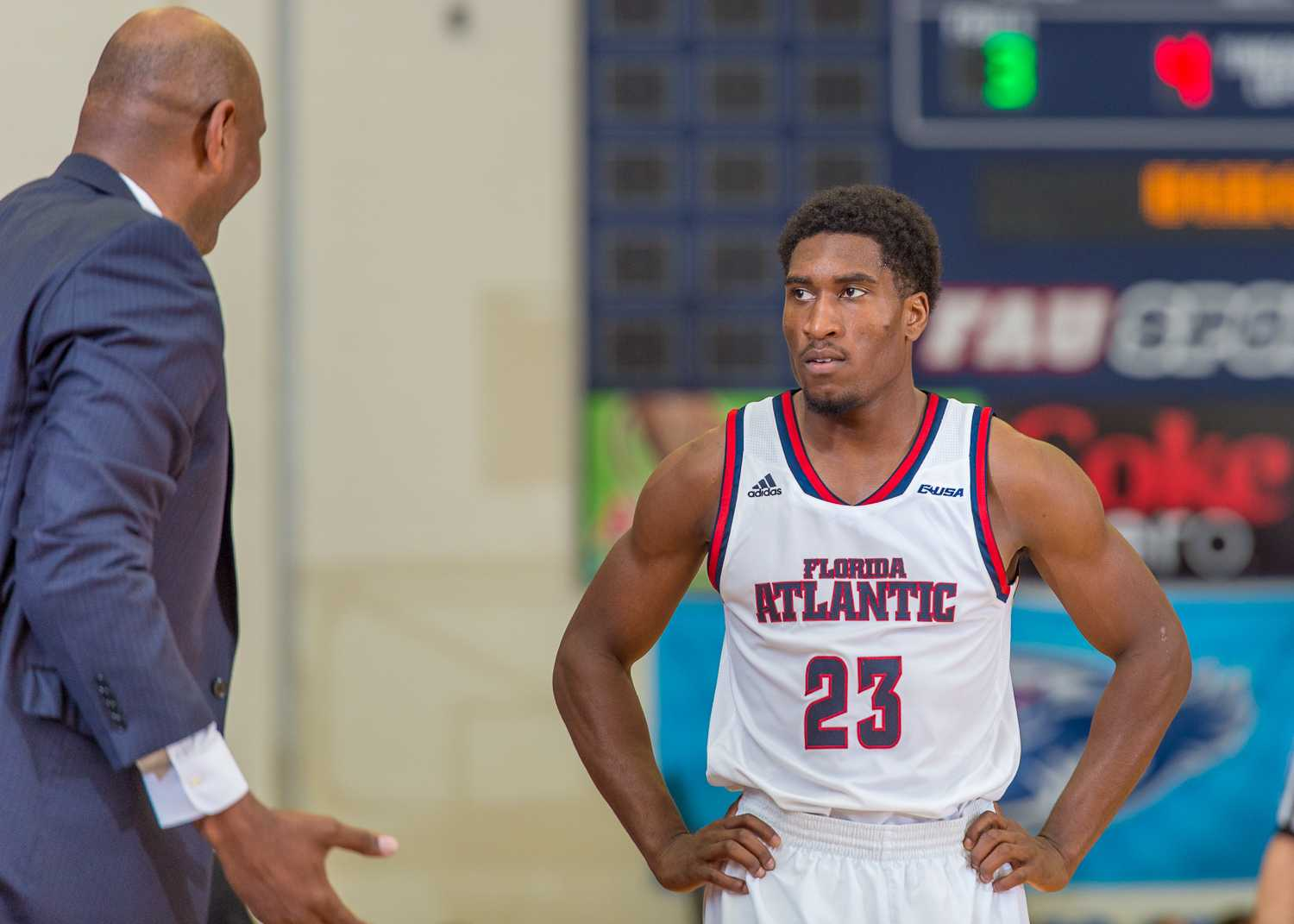 FAU head coach Michael Curry speaks with guard Solomon Poole (23) during a break in the second half.  Poole was 3-for-13 on field goals and 2-for-5 on 3-pointers.inside the arc in the loss on Feb. 5.