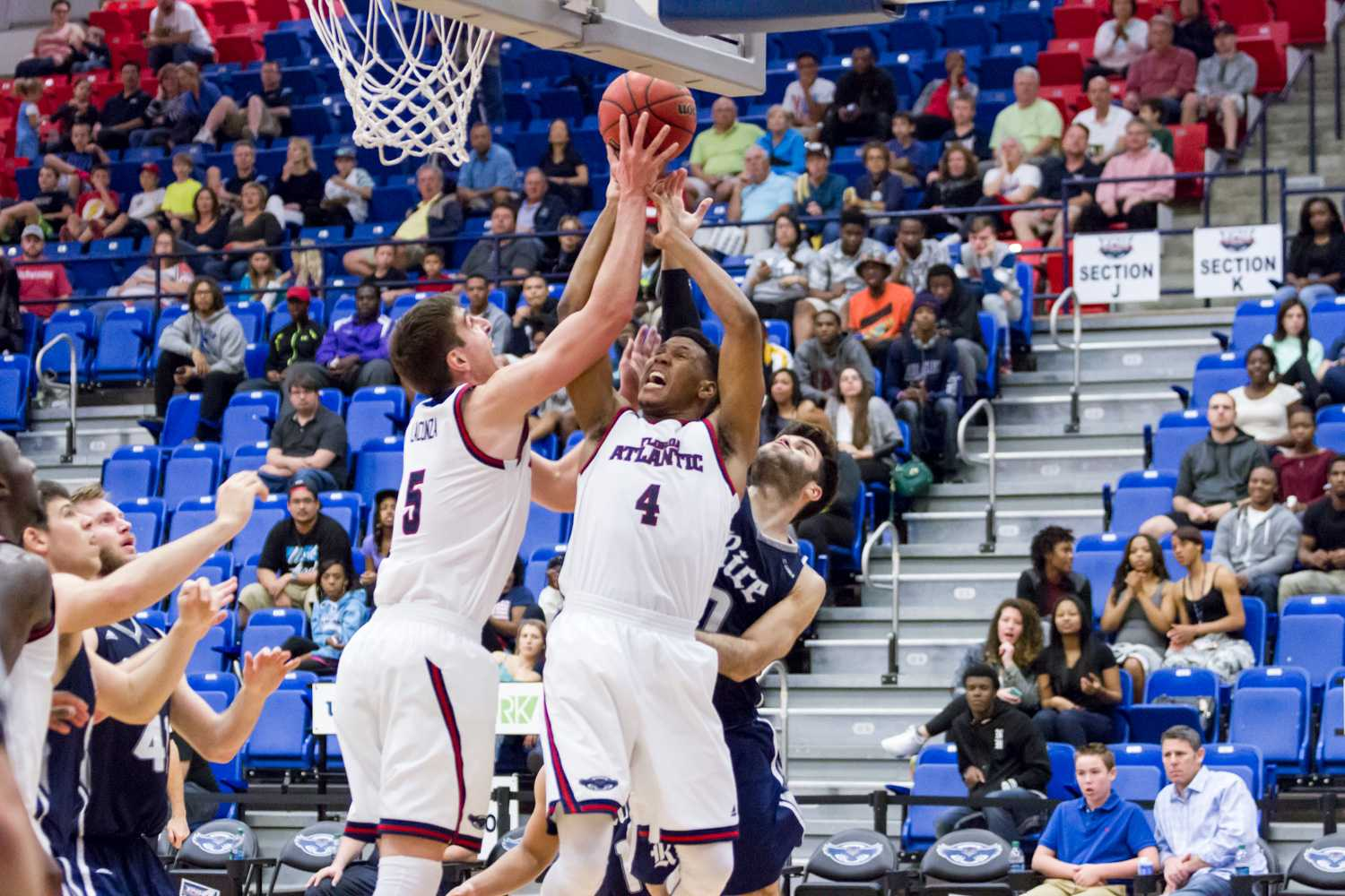 Freshman guard Justin Massey (4) and Lacunza (5) fight to secure a rebound. The Owls out-rebounded Rice 28-27, and Massey tied his career high with eight rebounds.
