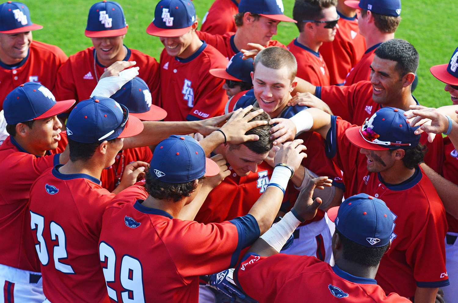 Outfielder Brandon Sanger (center) is swarmed by teammates after hitting a two-run home run in the bottom of the first inning for the last game of the series.