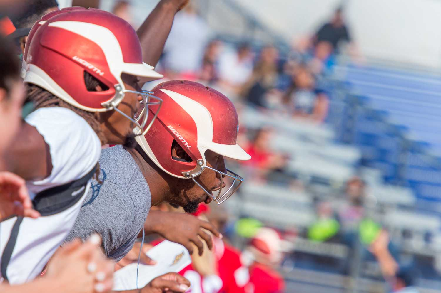 Quarterback Jaquez Johnson cheers on the softball team during their game against UCF, while him and other football players wear softball helmets.