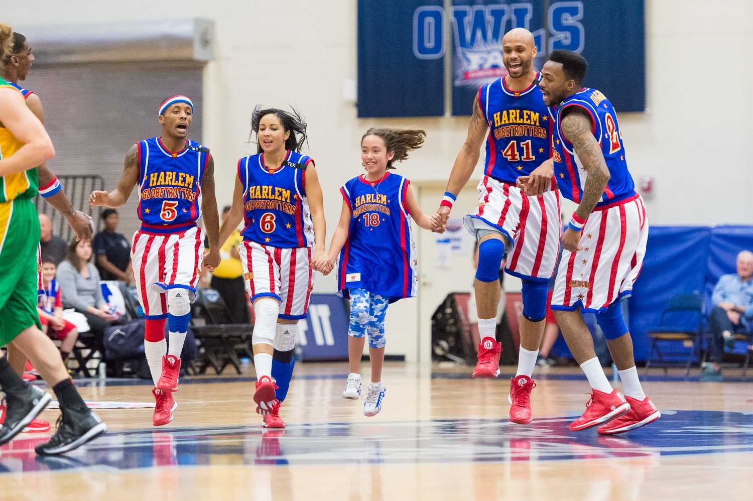 Members of the Globetrotters skip around the court with a member of the audience.
