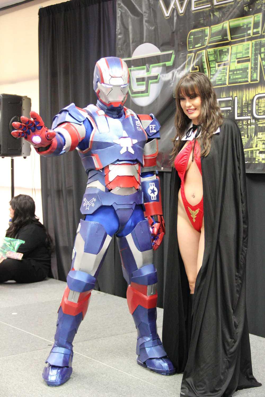 David Rodriguez as The Iron Patriot and Liza Rasija as Vampirella pose on stage before the Iron Patriot de-suits.