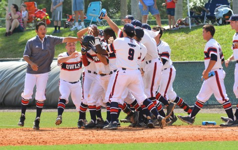 Third baseman Ricky Santiago is swarmed by his team as his extra innings sacrifice hit wins the Sunday game for the Owls. Michelle Friswell | Associate Editor
