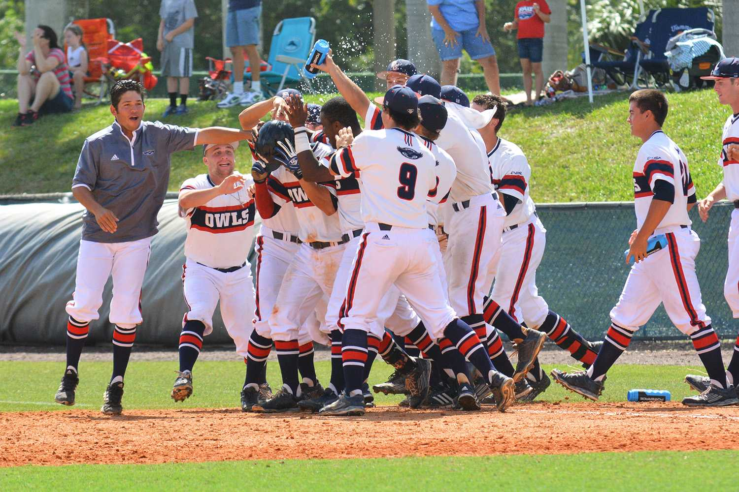 Third baseman Ricky Santiago is swarmed by his team as his extra innings sacrifice hit wins the Sunday game for the Owls. Michelle Friswell   Associate Editor