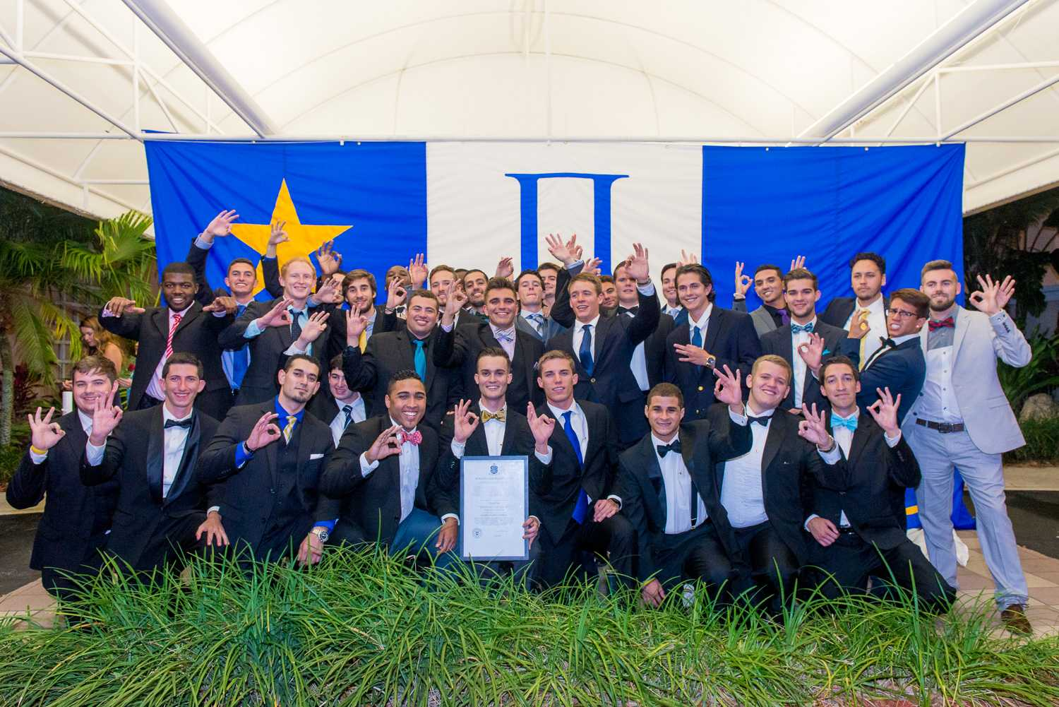 The brothers of Pi Kappa Phi pose for a photo with their flag after the chartering ceremony on Saturday night.  Max Jackson | Photo Editor