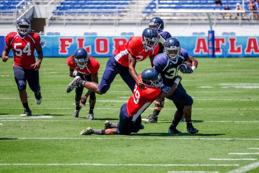 Senior Jeremy Gaskins avoids two defenders while getting a 1st down. Mohammed F Emran | Web Editor.