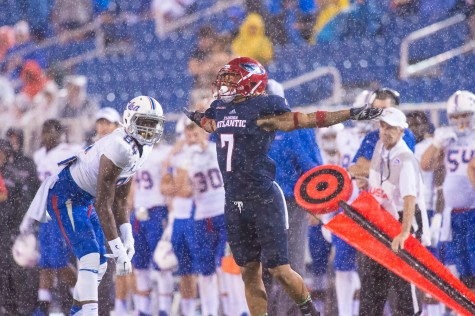 Defensive Back Cre'von LeBlanc stretches his arms out in the rain during last year's game versus Tulsa. Photo by Max Jackson