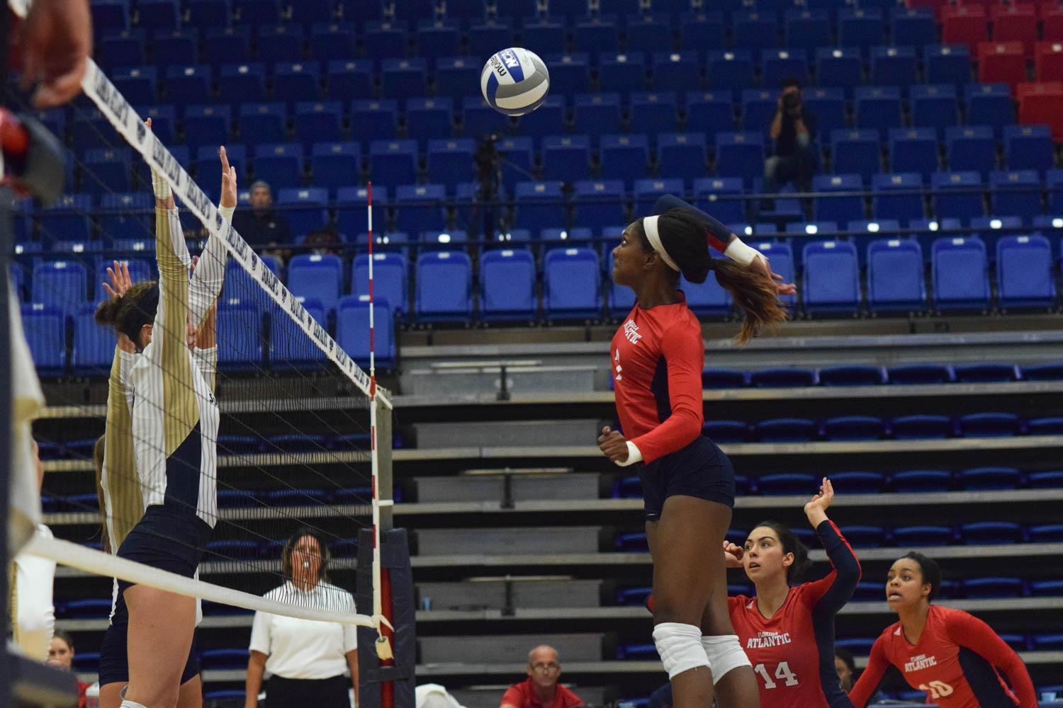 Senior middle blocker Brittany Brown spikes the ball past two Eagles defenders during the first set of their match during the FAU Invitational tournament. Ryan Lynch | Sports Editor