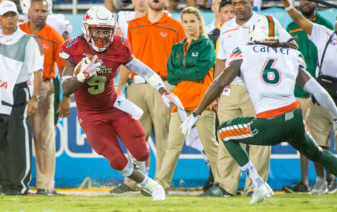 Sophomore running back Greg Howell attempts to get past Miami defensive back Jamal Carter during Friday's 44-20 loss. Max Jackson| Staff Photographer