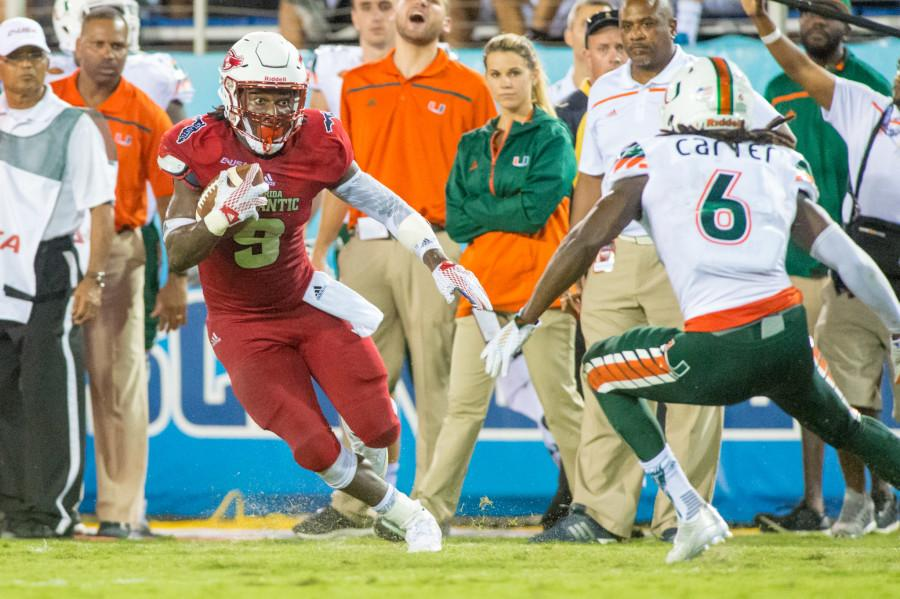 Sophomore+running+back+Greg+Howell+attempts+to+get+past+Miami+defensive+back+Jamal+Carter+during+Friday%27s+44-20+loss.+Max+Jackson%7C+Staff+Photographer