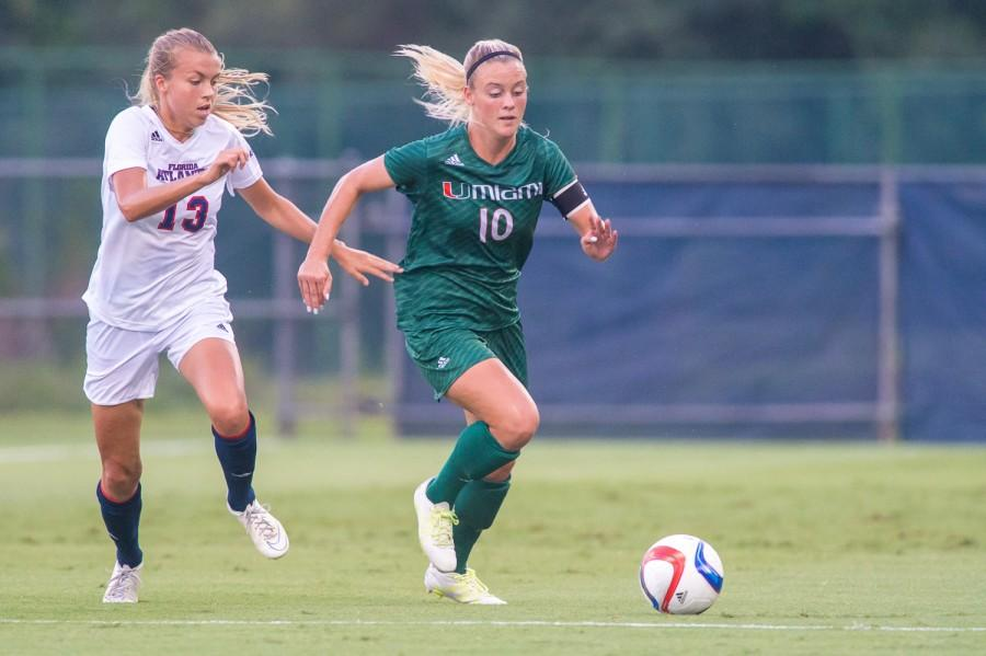Owls forward Asta Arnadottir (13) and Hurricanes defender Natalie Moik (10) vie for the ball in front of Miami's goal during the first half of Friday's game. Arnadottir scored twice during the 3-1 win. Photo by Max Jackson|Staff Photographer