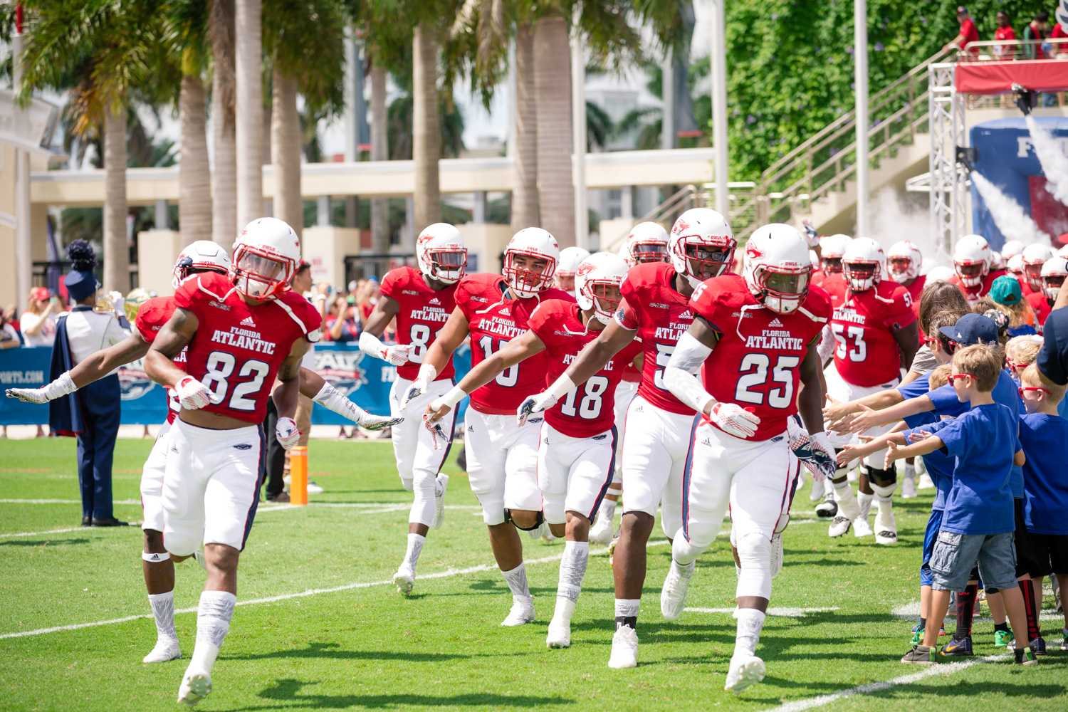 FAU Owls high-five fans as they make their way on to the field at the start of the game against the Buffalo Bulls Saturday afternoon. Brandon Harrington | Photo Editor