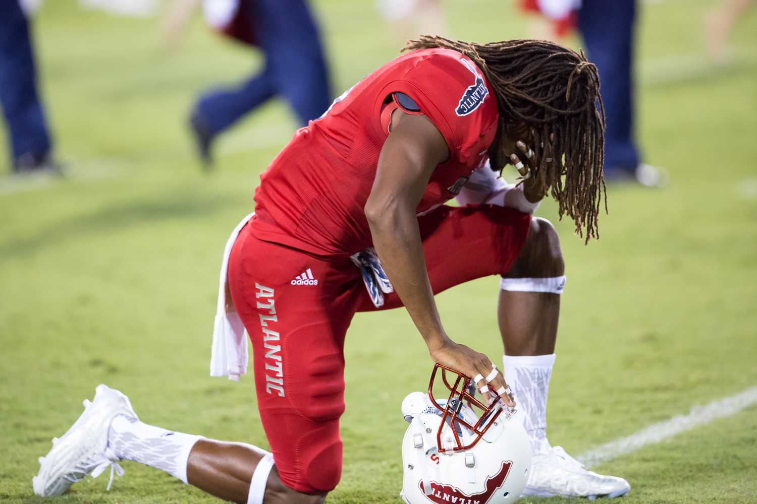 FAU redshirt sophomore cornerback Ronnie Scott (5) goes down on one knee to pray before the start of the game against the University of Miami Hurricanes. The Hurricanes beat the Owls 44-20 Friday night. Brandon Harrington | Contributing Photographer
