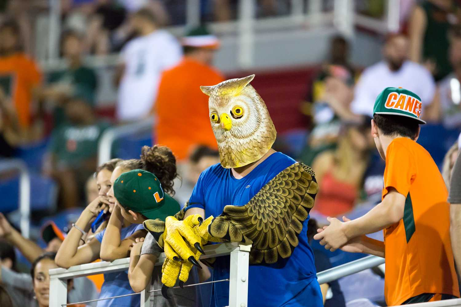 Not letting the weather delay stop them, an Owls fan stands his ground while surrounded by Hurricane fans during the UM-FAU game Friday night. Brandon Harrington | Contributing Photographer
