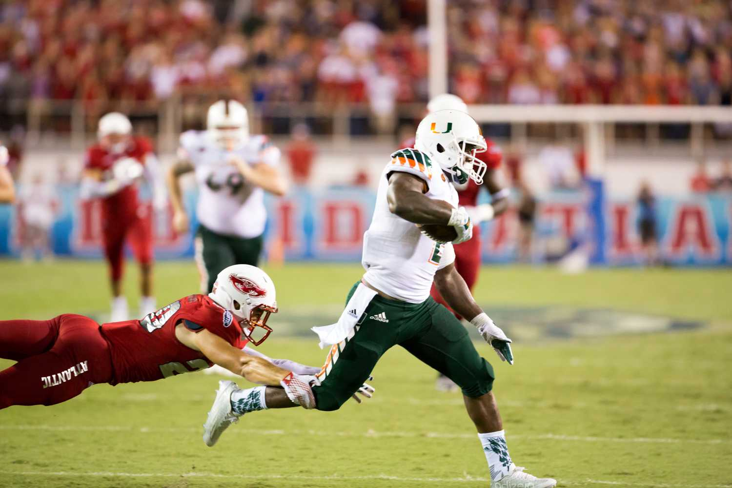 FAU redshirt freshman defensive back Jake Stoshak (20) dives to stop UM sophomore running back Joseph Yearby (2) early in the first quarter Friday night. Stoshak ended the game with 10 tackles. Brandon Harrington | Contributing Photographer