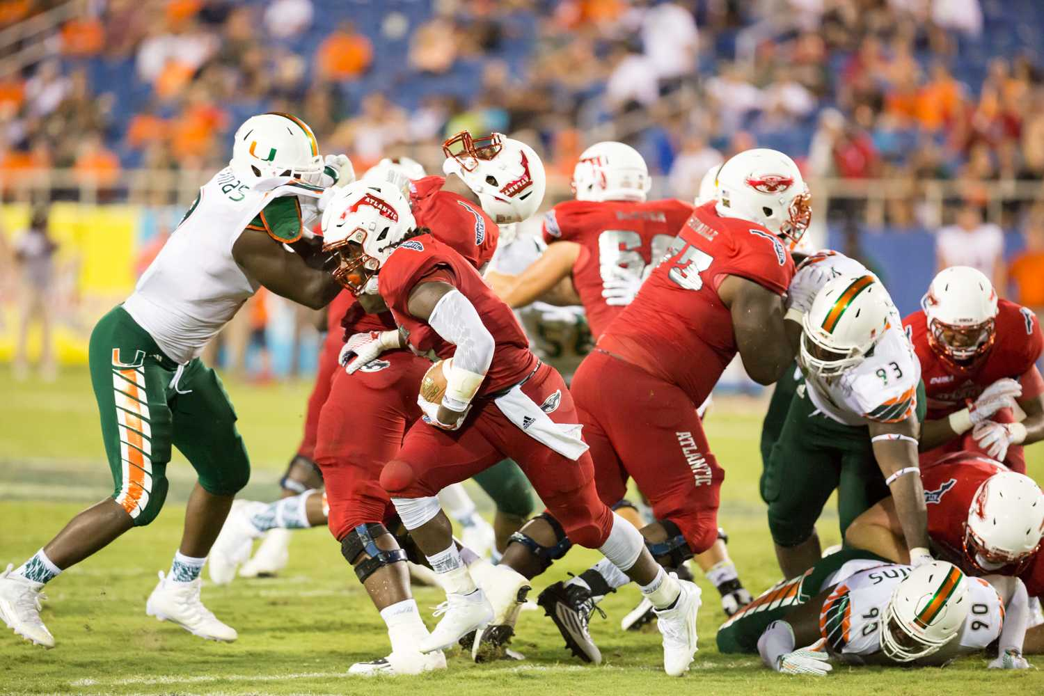 "FAU sophomore running back Greg ""Buddy"" Howell (9) rushes past as his teammates make a path for him in the second half of Friday night's game. Howell ended the game with 78 rushing yards. Brandon Harrington 