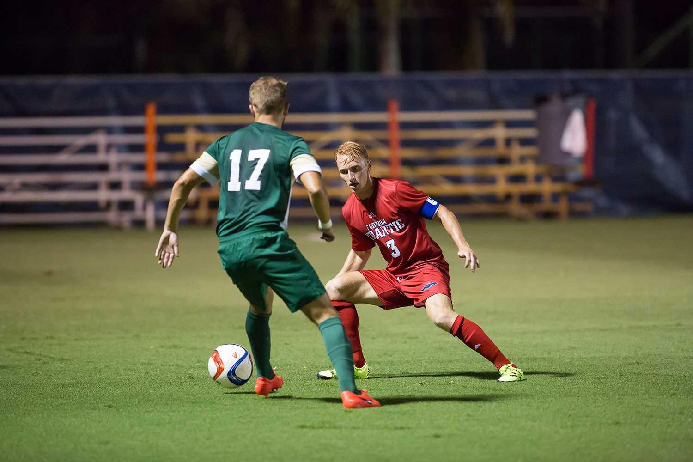 Freshman defender Donovan Henry (3) tries to steal the ball from Dolphins junior midfielder Jack Burns (17). Brandon Harrington | Contributing Photographer