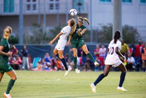 Senior midfielder Claire Emslie (9) jumps for a header against Miami redshirt junior defender Shannon McCarthy (8) during the first half of Friday's Game. Emslie had an assist on the final goal of the 3-1 win. Photo by Brandon Harrington|Contributing Photographer