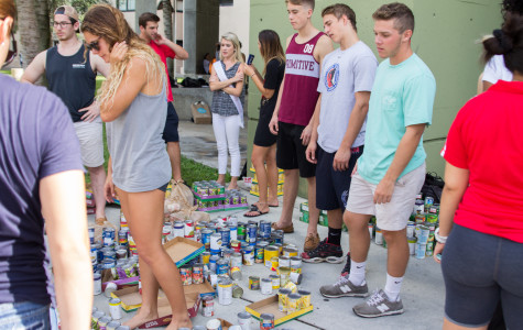 Students try to build a superhero sculpture out of canned goods to celebrate 2015's Homecoming theme