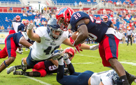 FAU running back Marcus Clark (20) steps out of bounds before being tackled by Rice defensive end Brady White (40). Clark had three carries for a total of 48 yards on the day. Max Jackson | Staff Photographer