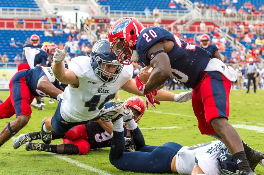 FAU+running+back+Marcus+Clark+%2820%29+steps+out+of+bounds+before+being+tackled+by+Rice+defensive+end+Brady+White+%2840%29.+Clark+had+three+carries+for+a+total+of+48+yards+on+the+day.+Max+Jackson+%7C+Staff+Photographer+